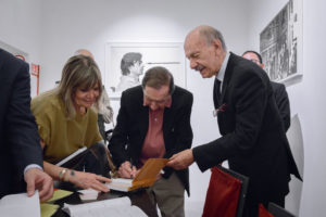 Milton Gendel signs a book in the presence of Ovidio Jacorossi.